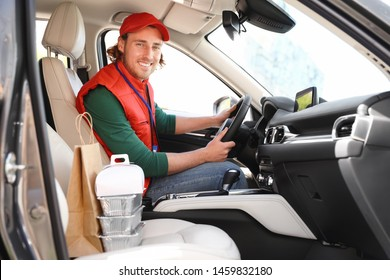 Male courier with orders in car. Food delivery service