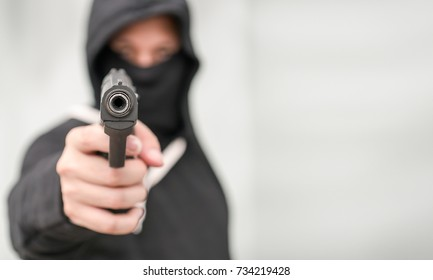 The male criminal in action of attacking with hand gun pointing gun to target in front. Isolated on gray background. The concept of crime for presentation slide.