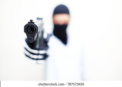 The male criminal in action of attacking with hand gun. Isolated on white background. The concept of crime for presentation slide. Focus at Gun.