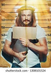 Male criminal suspect in the image of Jesus holds a laptop and a bottle of alcohol in his hand, is photographed against the background of the growth wall. Creative religious concept