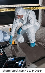 male criminologist in protective suit and latex gloves collecting evidence at crime scene with corpse