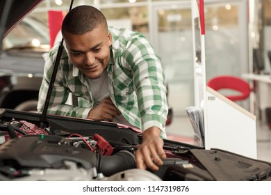 Male customer checking out engine of a new car for sale. Attractive cheerful man examining motor of an auto, while choosing vehicle to buy at the dealership. Horsepower, technology, machinery concept