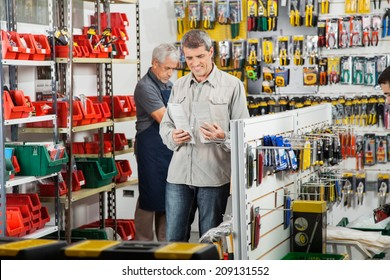 Male customer choosing soldering iron with worker working in background at hardware store