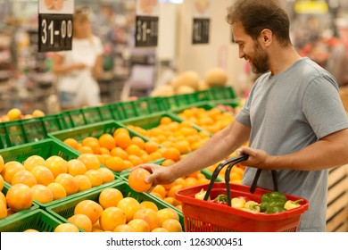 Male customer holding fresh orange and choosing citruses. Bearded man standing in supermarket in fruit section and do shopping. Man holding red basket full of products.