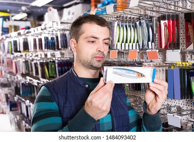 male customer  looking fishing lures near stand in the sports shop
