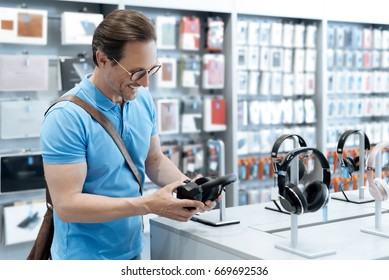 Male customer looking at headphones at store