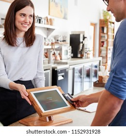 Male customer makes contactless card payment at coffee shop
