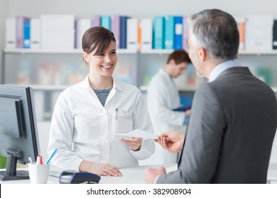 Male customer at the pharmacy, he is giving to the smiling pharmacist a prescription, healthcare concept