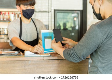 Male customer with protective mask paying bill by cell phone in cafe.