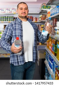 Male customer selecting bottle of water in  interior