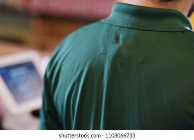 Male customer service worker with turned back. Service industry concept, with register in background