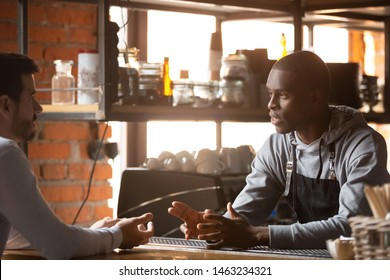 Male customer stand near counter talk with african American barista or waiter, millennial man client speak with black barmen make order in bar or restaurant, place manager have conversation with staff