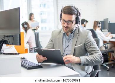 Männlicher Kundenbetreuer mit Zwischenablage im Büro