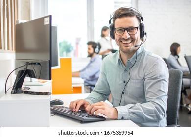 Männlicher Kundendienst-Telefonanbieter mit Headset, der im Callcenter arbeitet. Gruppe von im Büro tätigen Vertriebsmitarbeitern.