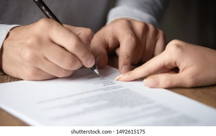 Male customer write signature on contract meeting lawyer solicitor, businessman client buyer ready to sign employment insurance sale purchase employment agreement concept make deal, close up view