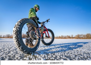 a male cyclist with his fat mountain bike on a frozen lake in northern Colorado, wide angle lens perspective