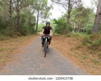 male cyclist with panniers/bike bags front view on paved road during sunset
