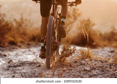 Male cyclist riding his full suspension mountain bike on dusty trail