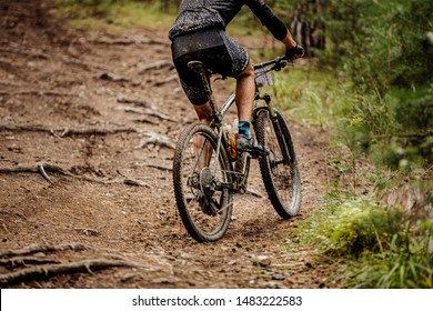 male cyclist riding uphill mountainbike race in forest