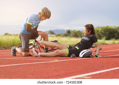 Male cyclists first aid woman cyclists cramp on track in concept team, together and sport.