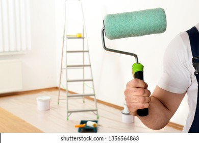 Male decorator with paint roller in empty room, closeup. Space for text