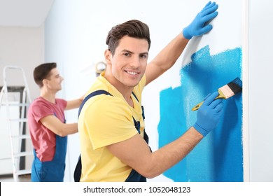 Male decorator painting wall with brush indoors