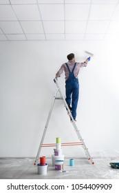 Male decorator painting wall with roller in empty room