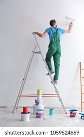 Male decorator painting wall with roller indoors