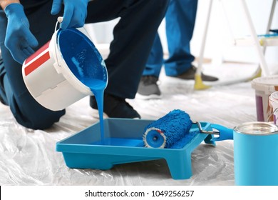 Male decorator pouring paint into tray indoors