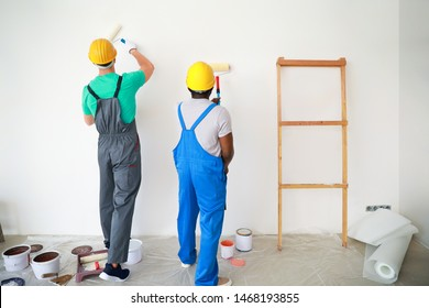 Male decorators painting light wall