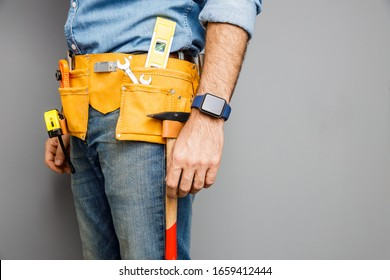 Male in denim wear is standing with belt full of hand instruments for repairing home. Isolated on grey background
