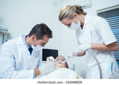 Male dentist with assistant examining girls teeth in the dentists chair
