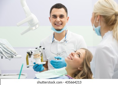Male dentist in the dental cabinet. He is in the white uniform with blue latex gloves, blue mask, binocular loupes. He sits on the chair and holds an articulator with teeth mould.