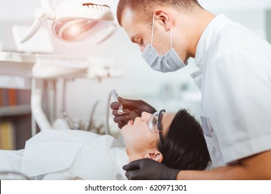 Male dentist with dental drill treating female patient teeth at dental clinic