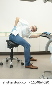 Male dentist exercising in his office waiting for patient - stretching