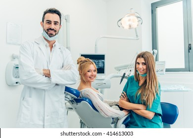 Male dentist, his assistant and female patient in dental practice