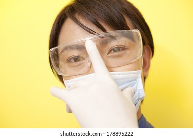 Male dentist pressing the finger on the goggles