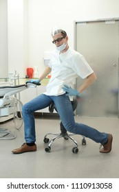 male dentist stretching his legs  in the office during break