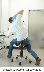 male dentist stretching his legs, arms and neck in the office during break