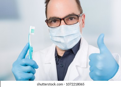 male dentist with a tooth brush, medical gloves and medical face mask shows thumb up