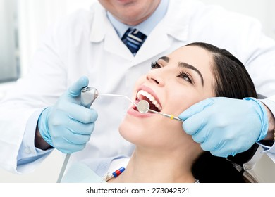 Male dentist whitening the woman teeth
