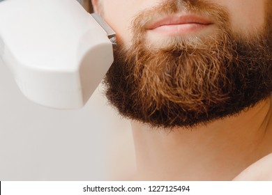 Male depilation laser hair removal beard and mustache procedure treatment in salon. Health and beauty concept.