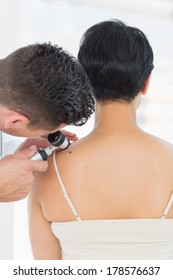 Male dermatologist examining mole on back of woman in clinic