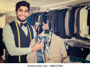 Male designer is picking up a tie for light jacket in the shop.