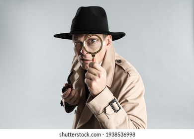 Male detective with smoking pipe looking through magnifying glass on grey background