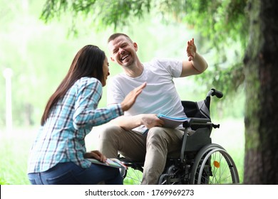 Male disabled man with girlfriend smiling on park walk portrait. Social disabitity adaptacion concept