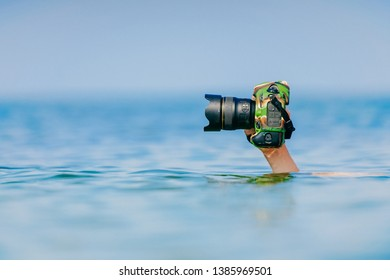 Male diver swimming under water and keeping dry and safety professional photocamera at his hand above water in ocean. Crazy photographer making photos from deep sea. Funny and dangerous hobby and job.