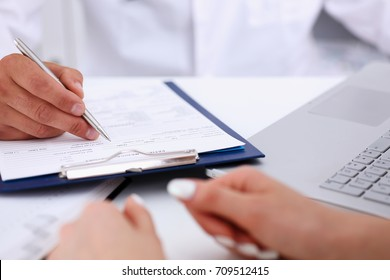 Male doctor arm hold silver pen filling patient complaints list clipped to pad. Physical, problem exam, er, disease prevention, ward round, visitor check, prescribe remedy, healthy lifestyle concept