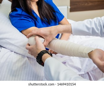 Male doctor bandaging hand of female patients. Medical concept
