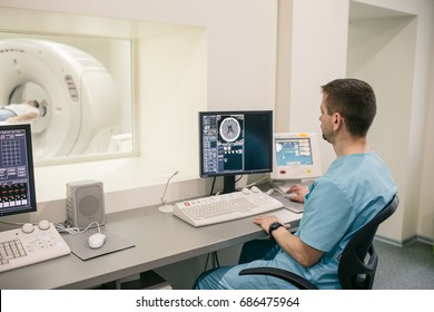 Male doctor in blue uniform seating near computer and looking on patient in magnetic resonance imaging machine